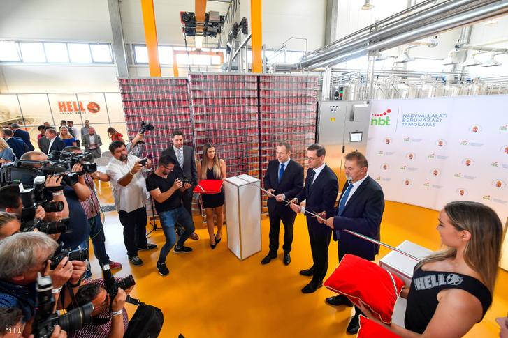 Varga Mihály pénzügyminiszter (k), Csereklye Barnabás, a Hell Energy Magyarország Kft. ügyvezető igazgatója (b) és Koncz Ferenc, a térség fideszes országgyűlési képviselője (j) átvágja a nemzeti színű szalagot a cég szikszói telephelyén épült új gyártósor átadásán 2019. július 19-én