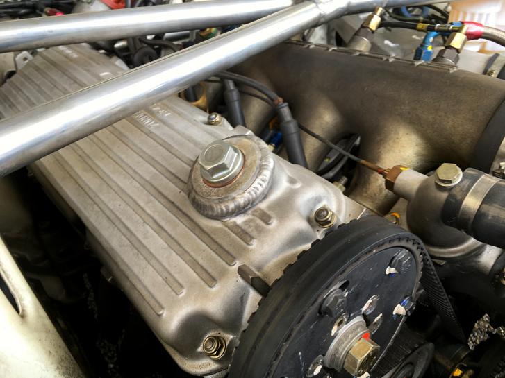Na, még egy Porsche, de ez orrmotoros. A 924 Turbo szelepfedelén az olajbeöntő sapkának csak a hűlt helyét láthatjuk, a száraz karteresre átalakított motorba már nem itt kel betölteni az olajat. A nyílás száját behegesztették, de azért a közepére egy csavart betekertek - gondolom azért néha itt is töltenek be pár csepp olajat, azért kell a szabaddá tehető furat