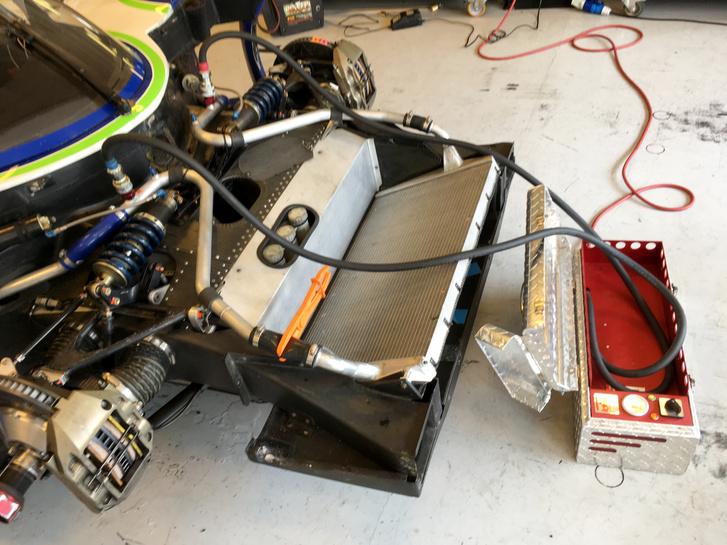 Tudjuk jól, hogy egy motort legjobban a hidegindítások gyilkolnak. Különösen igaz ez egy különleges versenymotorra. Ezért aztán már az előtt felmelegítik őket, hogy egyet is röffenne a motor: nagy teljesítményű vízmelegítőt kötnek a hűtővízkörre, és keringetik a dzsúszt a teljes rendszerben, már jóval az indítás előtt. Hogy ne dolgozzon a rendszer feleslegesen, a hűtőradiátorhoz vezető ágat elzárják (elnézést az életlen képért, szerintem már remegtem a gépészeti pornó túladagolástól)