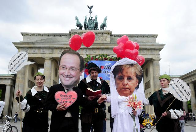 Berlini aktivisták Hollande és Merkel maszkban a Brandenburgi kapunál