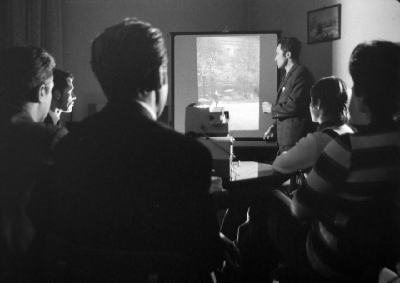 Az állambiztonság munkatársai operatív eszközzel készült titkos fotót értékelnek ki a diavetítőn. A titkos képrögzítést egészen a rendszer végnapjaiig folytatta az állambiztonság. Az 1989-es demonstrációkon is bőszen fényképeztek, ezek a fotók a kevés kivétel közé tartoznak, melyek fennmaradtak. A Belügyi Filmstúdió állambiztonsági technikákat bemutató filmjei egy kutyatelepre kerültek, véletlennek köszönhetően menekültek meg az enyészettől. Stáblisták nincsenek.