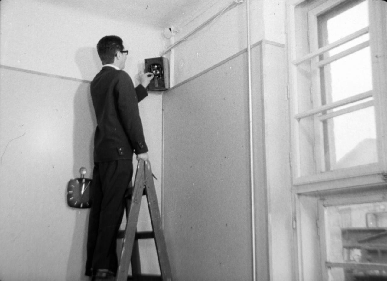 Rejtett fényképezőgép telepítése egy iroda rádióhangszórójába. A lenti képen már a hangszóró álcázási céllal visszatett hálóján keresztül készült megfigyelési fotót láthatjuk.