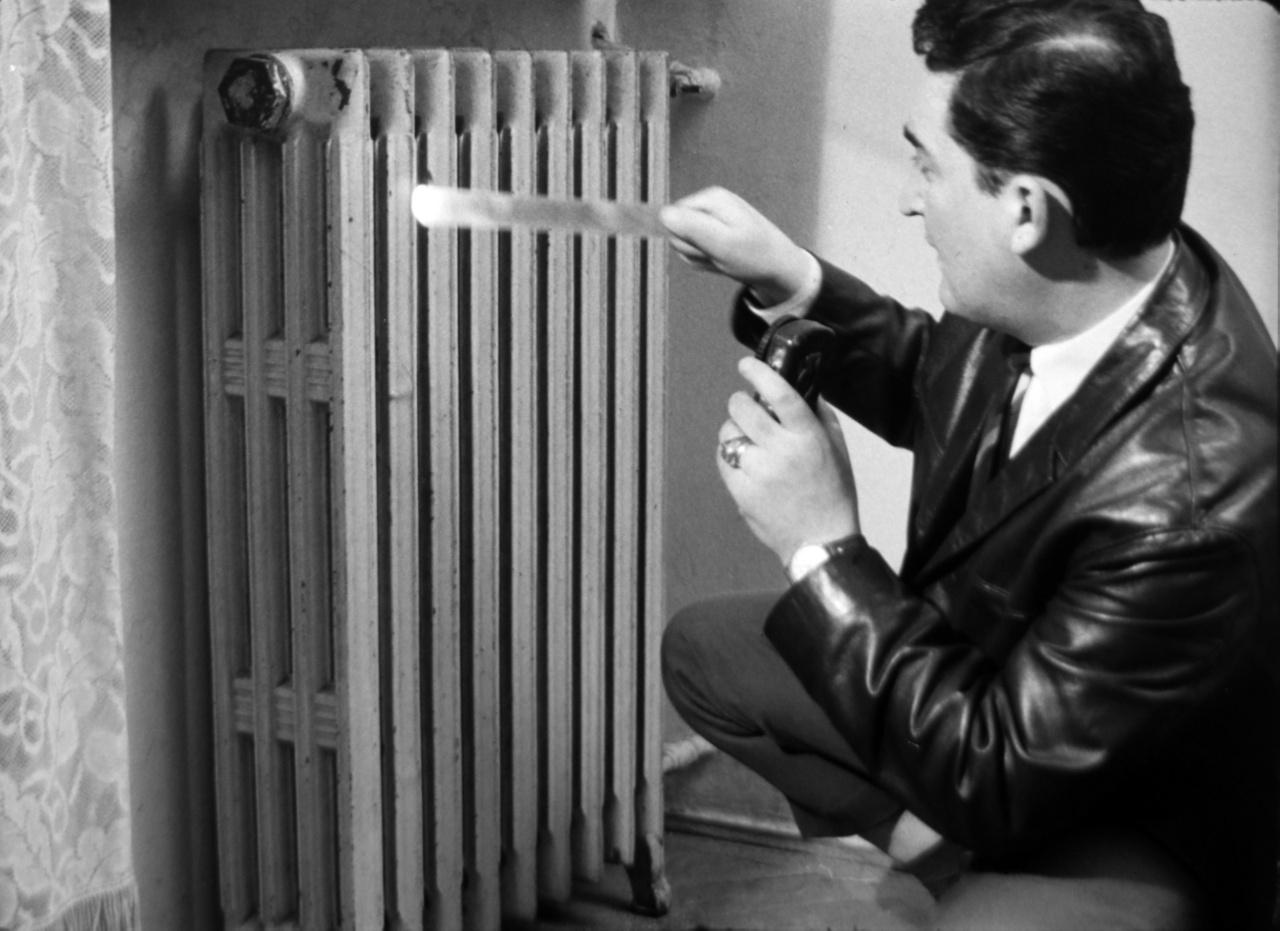 """""""A nyugodtság alapvető követelmény. Főhadnagy elvtárs! Csak azt szabad elmozdítani, ami feltétlenül szükséges, és mindent azonnal vissza kell tenni a helyére!"""" - hangzik el az 1958-as Titkos házkutatás című filmben. Az állambiztonsági bemutató fiktív valóságában természetesen valódi bűnözőkre gyűjtenek bizonyítékokat a távollétükben: a házkutatáson százdolláros bankjegyek, titkos kapcsolatokat tartalmazó gyanús névsor, WC-tartályba rejtett pisztoly, a zakózsebből még aktfotók is előkerülnek."""