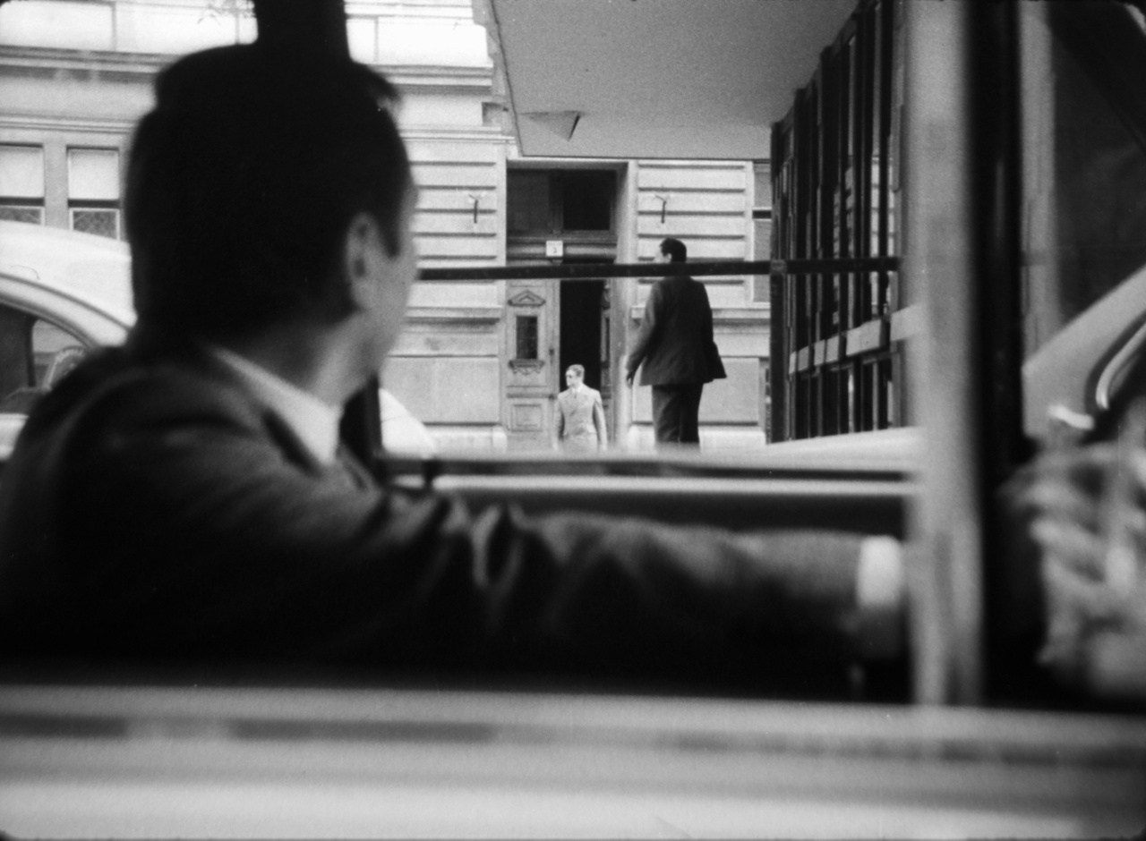 """A Titkos megfigyelés című film részlete egy átjáróházat mutat, felhívva a figyelmet arra, hogy minden kijáratot biztosítani kell. Az állambiztonsági szlengben """"kukkosnak"""" hívott figyelők általában a hierarchia alján voltak. A titkos tiszteket Müller Rolf tanulmánya szerint vagy a polgári életből, önkéntes jelentkezéssel, vagy a BM káderkutató munkája során a kerületi, munkahelyi párt- és KISZ-szervezetek javaslatai alapján vették fel, vagy pedig a belügy más területeiről helyezték át őket. A szellemi és fizikai alkalmasság paraméterei közé a jó megfigyelő és a környezethez való alkalmazkodási képességet, az átlagos, nem feltűnő testalkatot és a kiváló egészségi állapotot sorolták."""