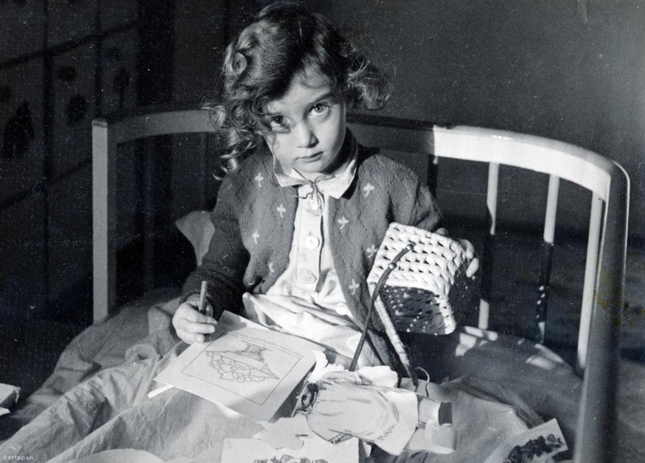 """Preisich Anikó otthon betegen, a Vadász Mihály (vele tervezték a Simplon-házat is) közreműködésével készült óvodai szekrénnyel a háttérbenRut 1935-ben, a Királyi Pál utcában német nyelvű óvodát indított, ahol tizenhat gyermekkel foglalkozott. """"Az óvodaszekrényben tizenhat rekesz volt, egy-egy minden óvodásgyerek részére. Ezeknek az emblémáit – nyuszit, mókust, csillagot stb. – Gabi társa, Vadász Miska rajzolta meg."""""""