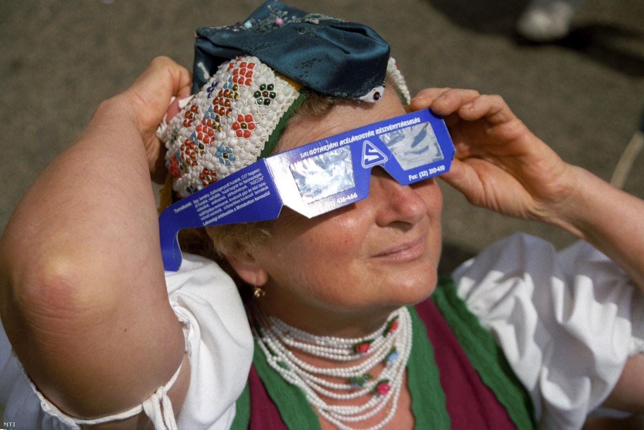 Népviseletbe öltözött asszony védõszemüveggel figyeli a napfogyatkozást Hollókõn. Az ultraibolya sugárzás túlnyomó részét kiszűrő, egyszerű szemüvegkeretbe foglalt fóliákat országszerte árusították, és a sajtó is figyelmeztette az embereket, hogy védőszemüveg nélkül az UV-sugárzás maradandó látáskárosodást okozhat.