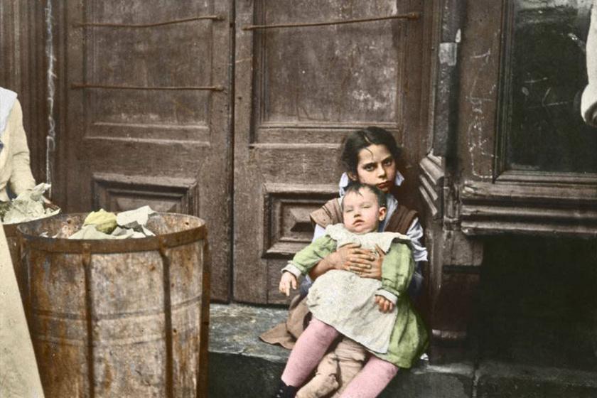 Egy kislány, karjában egy kisbabával az utcai szemetes mellett.