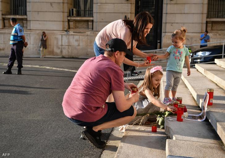 Egy család gyergyát gyújt a meggyilkolt Alexandra emlékére a bukaresti belügyminisztérium épületének lépcsőjén