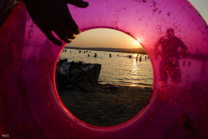 Strandolók a Velencei-tó partján naplementekor a Velence Korzó és Szabadstrandon