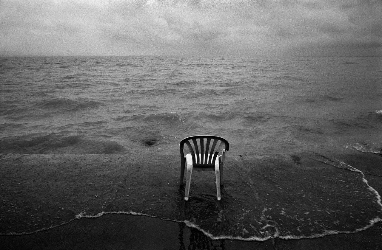 """Kempingszék egy magyar vízparton.A vízben maradéktalanul jelen vannak a világ alapvető vonásai – így az elmúlás is, írja Uhl Gabriella. A holttestek, mítoszok állandó partra sodródása a peremvidékek jellemzője. A part pedig gyakran áldozati felajánlások helyszíne: """"a mi vízbe fulladt halottjainké, az ő partra vetett tetemeiké."""""""