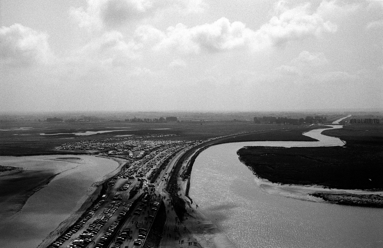 Strand és parkoló egy folyó partján Franciaországban.Nem csak az ember formálja a környezetét, de a környezet is formál minket a változásaival. Hiszen a víz mennyisége sem állandó: gyakran túl kevés pusztító aszálykor, sokszor pedig túl sok van belőle árvíz idején.