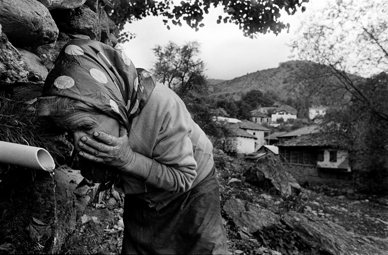 """Arcát mosó asszony Észak-Macedóniában.A víz """"az a kincs, ami mindig elfolyik az ujjaink között, és sohasem fogy el"""", mondja a kurátor. Egy mindig mozgásban lévő, rögzíthetetlen metafora, amiben egy dolog mindig egy másikhoz vezet."""