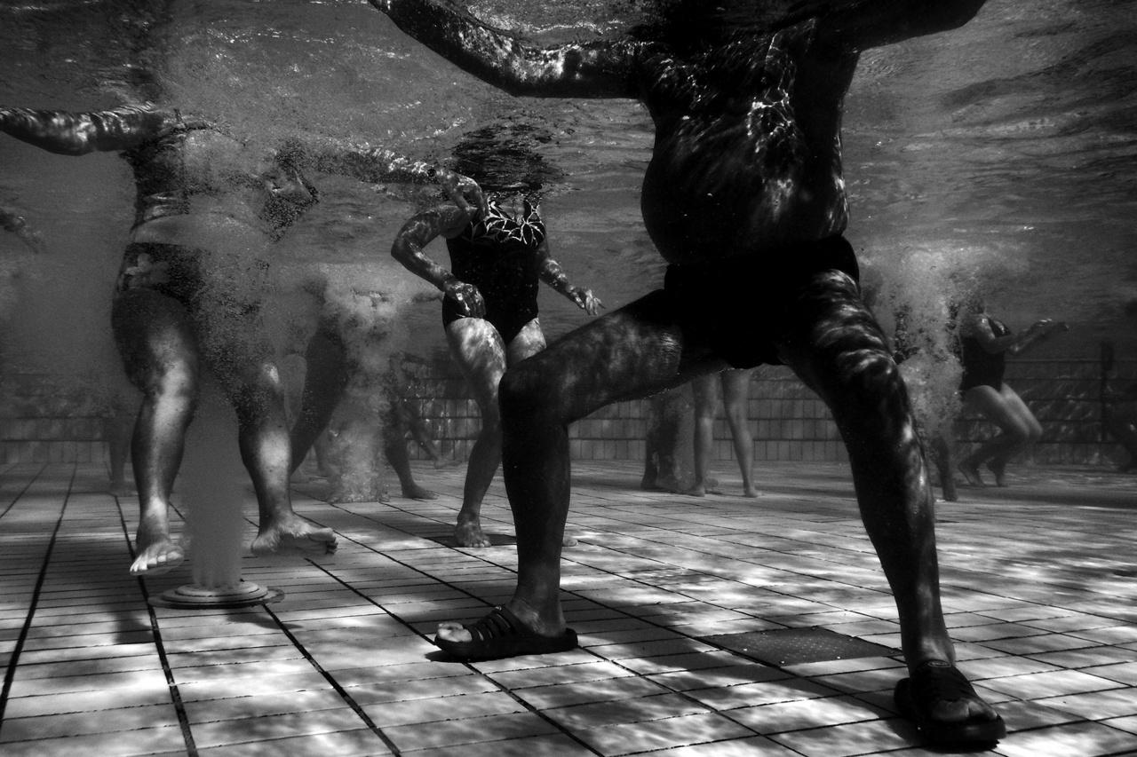 """Medence a Széchenyi Gyógyfürdőben, Budapesten.A gyógyfürdő vize a főváros második legmélyebb kútjából érkezik, 1246 méter mélyről, 76 fokos hőmérsékleten. A fotográfus beválogatta a """"Szecskában"""", Európa egyik legnagyobb fürdőkomplexumában készült képeit is az Aqua sorozatba."""