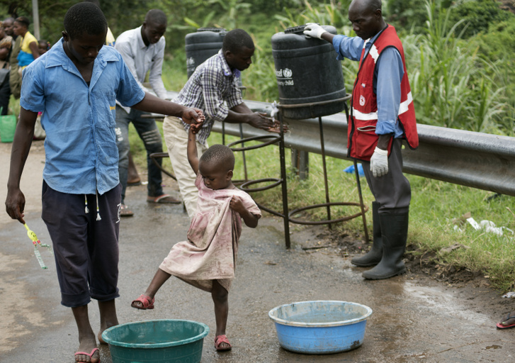 Apa gyermekével a Kongó és Uganda közti határon fölállított ebolaellenőrző ponton