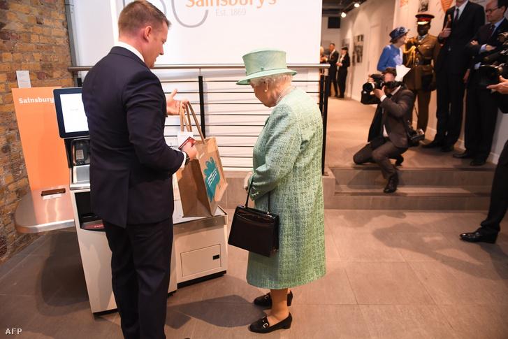 II. Erzsébet királynő nézi a bevásárlóautomatát a londoni Covent Garden egyik eredeti Sainsburys üzletének másolatában 2019. május 22-én, az üzlet 150. évfordulója alkalmából. Láthatóan nem nejlonzacskóban vásárolt.