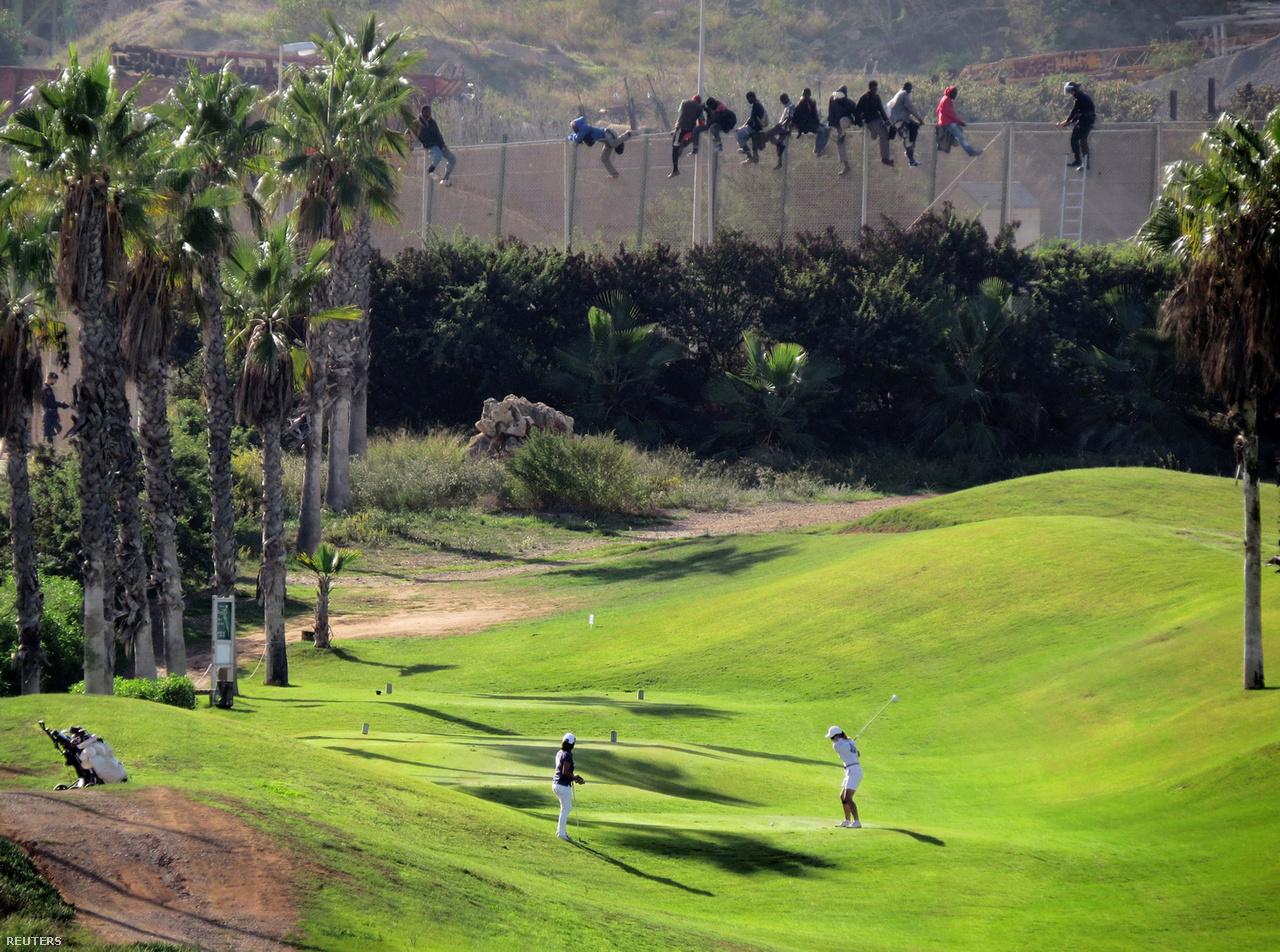 Golfozók Meillában, a háttérben pedig a hat méter magas kerítés tetejére mászó migránsok 2014-ben. A két észak-marokkói spanyol enklávé, Melilla és Ceuta köré az 1990-es években emeltek kerítéseket. Ezek jelentik az egyetlen szárazföldi határokat Európa és Afrika között, éppen ezért rengetegen próbáltak itt menedéket kérni. Csak a kép készítésének napján 400 menekült próbálkozott a bejutással. Melillánál hat méter magasra emelték meg a kerítést, folyamatosan monitorozzák infravörös kamerákkal, mozgásérzékelőkkel a környéket. A spanyol rendőrség nagyjából egy perc alatt tud reagálni egy bejutási kísérletre. Az elmúlt években már csökkent az érkezők száma, sokan inkább a tengeri útvonallal próbálkoznak.