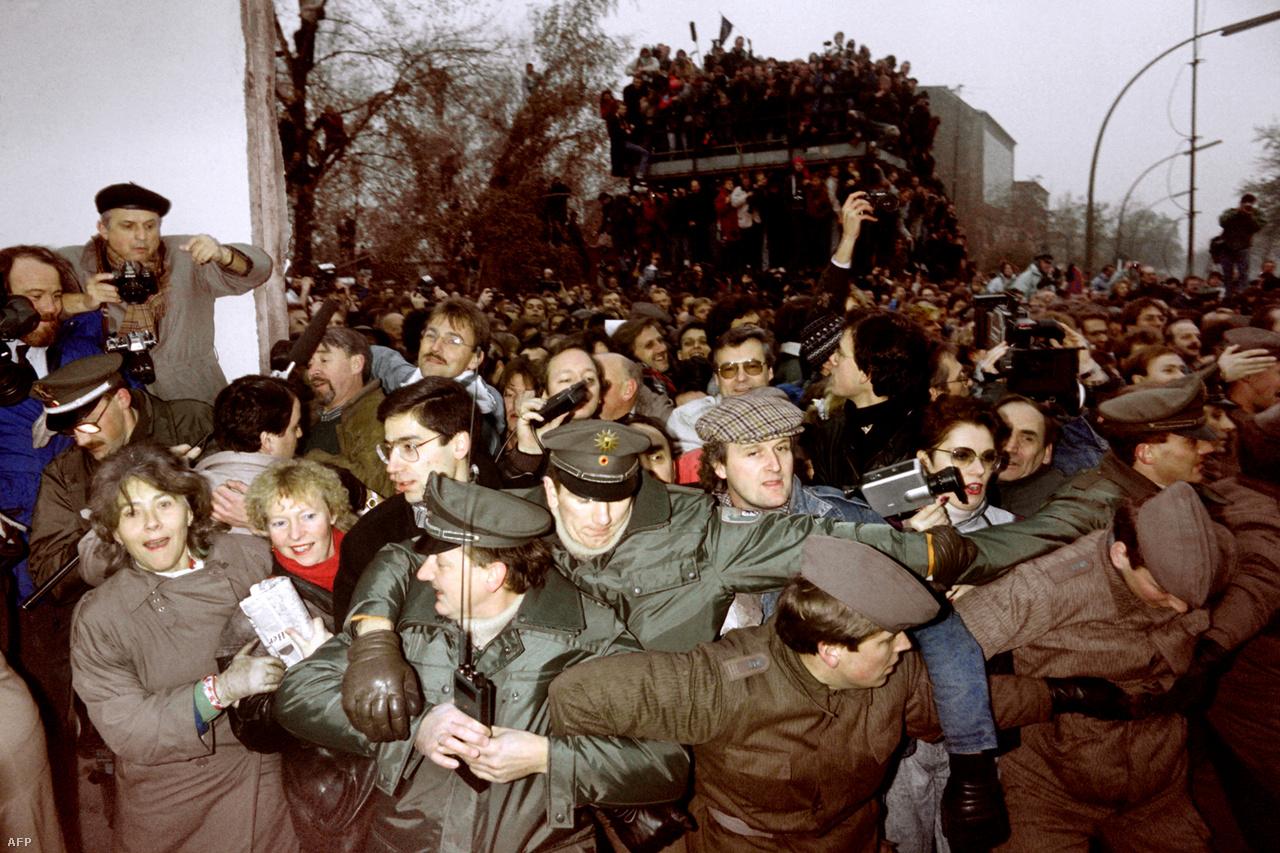 Ikonikus képek egyike, ahogy 1989. november 12-én rendőrök próbálják fékezni a megnyílt berlini falon átáramló kelet-német tömegeket. 1961. augusztus 13-án, vasárnap a berliniek arra ébredtek, hogy éjszaka az utcákat drótkerítéssel zárták le, a villamos- és metróvonalakat átvágták, de még a temetők közepére is szögesdrótot húztak, a berlini fal pedig a Kelet-Európában élők elnyomásának legfontosabb jelképe lett, és 29 éves fennállása alatt mindvégig az is maradt.