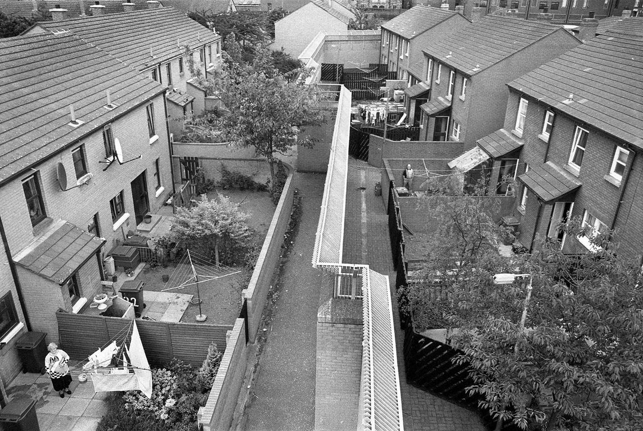 Békevonalak felülről Belfast keleti részén, 1994-ben. 1960 és 1998 között az Írország újraegyesítéséért küzdő észak-írországi katolikus-republikánusok és a brit uniópárti protestáns-lojalisták fegyveres csoportjai harcoltak egymással. A konfliktus közel 3600 ember életébe került, mielőtt 1998-ban megkötötték a Nagypénteki Egyezményt. A falak azonban azóta is állnak. Egyes részeken rendőrök által ellenőrzött kapuk vannak, amiken nappal át lehet járni, de éjszakára bezárják ezeket.