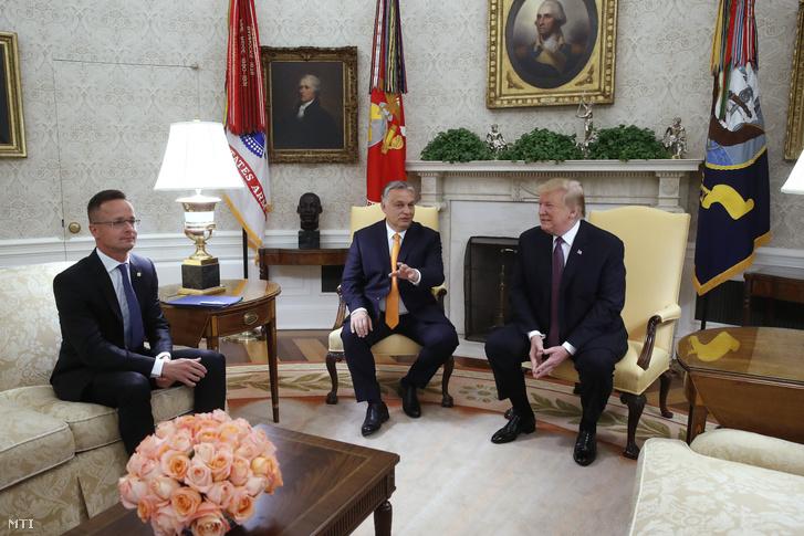 Donald Trump amerikai elnök és Orbán Viktor miniszterelnök megbeszélést folytat a washingtoni Fehér Ház Ovális irodájában 2019. május 13-án. Mellettük Szijjártó Péter külgazdasági és külügyminiszter.