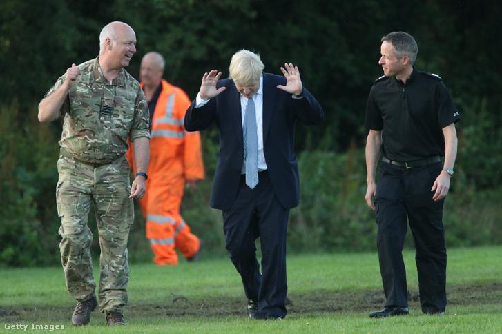 Boris Johnson miniszterelnök a gát mentési munkálataiért felelős szakértőkkel beszélget 2019. augusztus 2-án Whaley Bridge-ben.