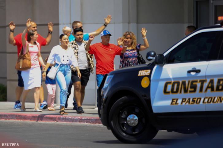 A vásárlók felemelt kézzel távoznak az El Pasó-i Walmart áruházból a lövöldözést követően 2019. augusztus 3-án.