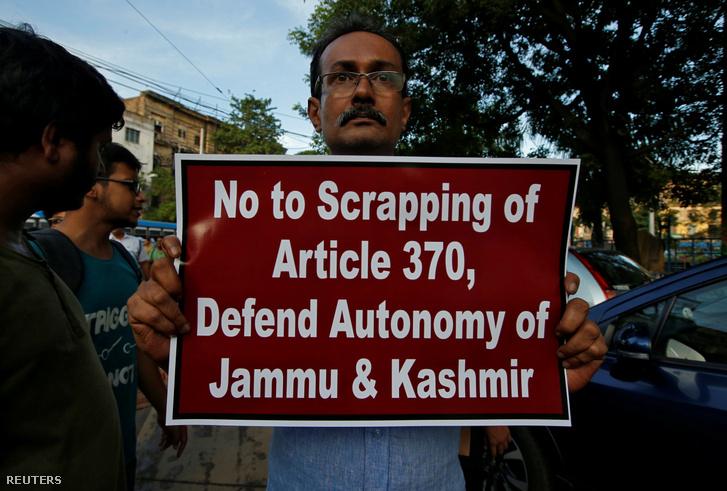 Egy ember plakátot mutat az alkotmány különleges státusának lebontása elleni tiltakozás során