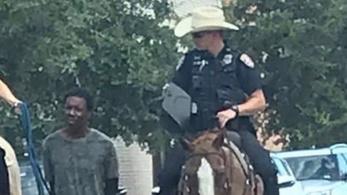 Két fehér rendőr lovon ülve, vezetőszáron vonszol maga után egy bilincsbe vert fekete férfit