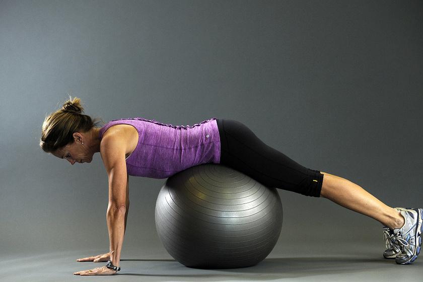 Helyezkedj el úgy, hogy a labda a hasad alatt legyen, de leérjen a földre a karod és a lábad is.