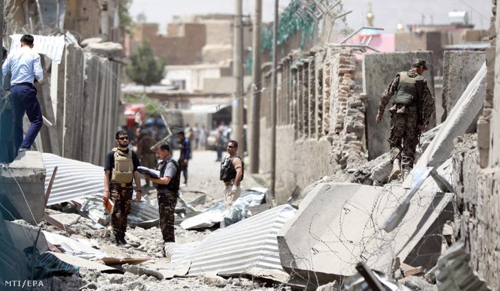 Afgán rendfenntartók helyszínelnek Kabulban ahol autóba rejtett pokolgép robbant egy rendõrségi épület bejáratánál 2019. augusztus 7-én. A detonációban legkevesebb 95-en megsebesültek halálos áldozatokról egyelőre nem tudni. A merényletet tálib lázadók vállalták magukra.