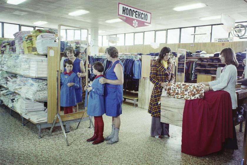 Az iskolaköpeny akkoriban még kötelező volt, egyfajta egyenruhaként, ám többféle fazon is létezett. A gödöllői, Szabadság téri áruházban így próbálta új köpenyét egy kislány 1974-ben.