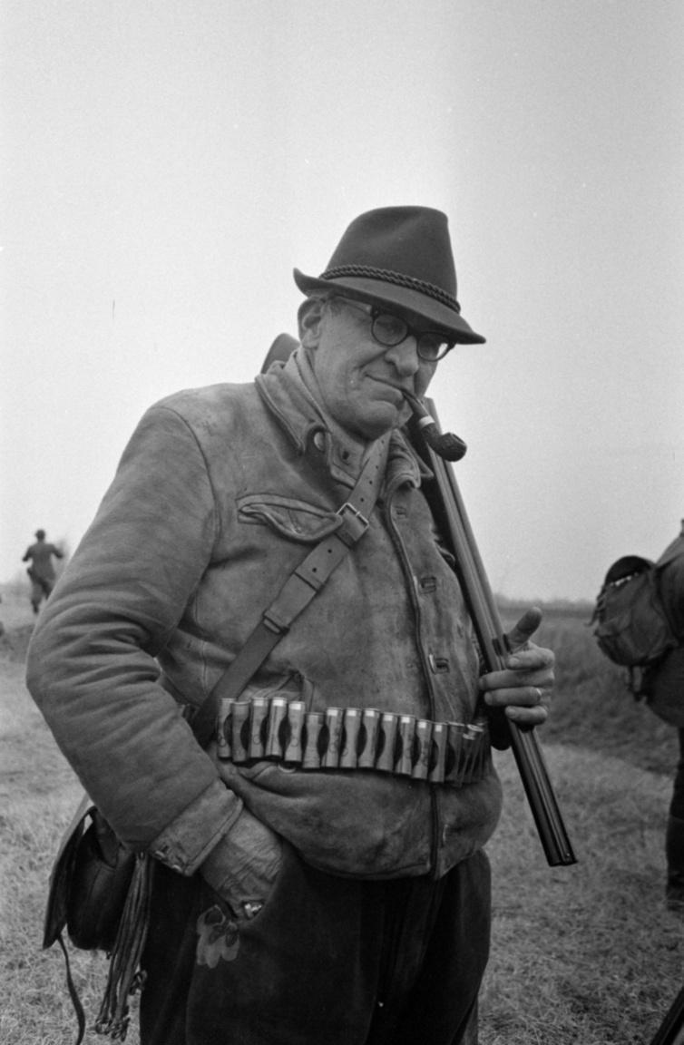 """Herr Reichert, aki talán csak Hansi (1966)Alex Reichert, így hívják a képen szereplő mainz-i vadászt, aki a szaklapban egy évvel korábban már fotózott, a debreceni Nagyerdőbe immár rendszeresen visszatérő társaival érkezett tíznapos őzlesre. A külföldi társaságokat kalauzoló magyar vadászok nem mindig ragaszkodtak a körülményeskedő megszólításokhoz, inkább leegyszerűsítették a névproblémát. """"Nekem minden külföldi Hanzi, és úgy is bánok velük. Tele vannak dohánnyal, fizessenek a szórakozásukért. Én sem leszek olcsójános akkor, amikor a vadászat eladásakor az állam sem az. Arról leszoktam, hogy elkunyeráljak bármit is Hanzitól, de már tudja, hogy valamilyen értékesebb ajándék kijár nekem""""– magyarázta egyikük a nyolcvanas években."""