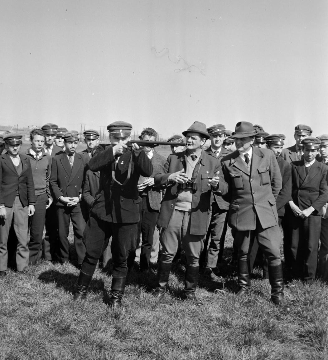 Terepgyakorlaton a balatonyfenyvesi vadászati iskolások, 19651959-ben indult meg a hároméves vadászati szakmunkásképzés Balatonfenyvesen. A vadász(vadőr)tanoncok az iskoalév öt hónapjában a Balatonnagybereki Állami Gazdaságban laktak és tanultak, hat hónapos gyakorlati képzésre pedig más-más szolgálati helyre osztották be őket. A Magyar Vadásznak készített riport idején negyven diákja volt az iskolának, közülük mindenki igyekezett rajta lenni a képen fején az iskola egyensapkájával.