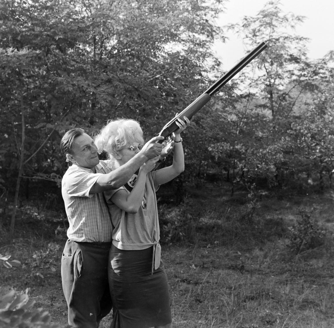 """Mire céloznak? Olasz nő és férfi lőfegyverrel, 1965A külföldi vadászok száma jelentősen nőtt: az 1959-1960-as idényben nyolcszázan jöttek, az 1961-1962-es időszakban már ezeregyszázan. Eleinte csak nyugatnémet vadászok, de 1962-ben olasz, osztrák, francia, belga, svéd, dán, norvég és angol vendégek is. Kádár egyébként nem volt híve a jó hangulatú, de fegyelmezetlen családi vadászatoknak – legalábbis az Egyetértés Vadásztársaságon belül. Ezért aztán idővel külön vadászatokat szerveztek a pártgyerekek és a pártfeleségek számára: megalakult az Ifjú Nimród Vadásztársaság, és kísérletet tettek a """"nimródhölgyek összefogására"""". Végül a láb alatt lévő nyugdíjasoktól is megtisztították az Egyetértést, őket az egymás között elfekvőként emlegetett Barátság Vadásztársaságba száműzték,"""