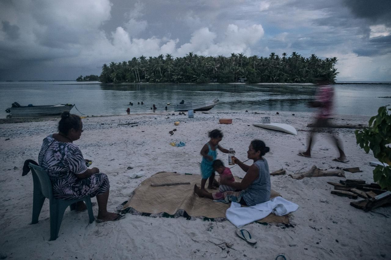 """Piknik a tengerparton a Tokelau-hoz tartozó Fenua Fala szigetecskén.  A régióban több olyan település van, ahol egyes házakat teljesen körülvesz a víz, amíg le nem vonul a dagály, így a lakók saját kis szigeteiken ragadnak. """"Az emberek folyamatosan attól rettegnek, hogy elveszítik otthonukat, hogy a gyermekeiket elviszi a víz. Ezért ha rossz idő van, egyes szülők odakötik őket valamilyen nehezebb tárgyakhoz a házban"""" - meséte Vlad Sokhin."""
