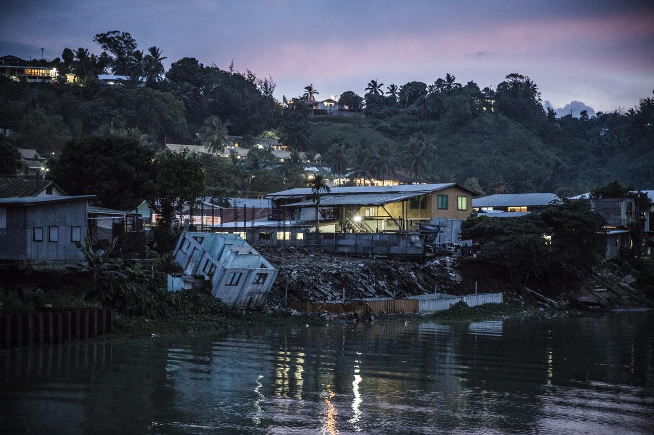 """Elhagyott, romos ház Mataniko folyó mellett a Salamon-szigetek fővárosában, Honiarában. 2014-ben súlyos árvíz sújtotta a területet, 22 ember meghalt, 9000 ember pedig elveszítette otthonát. A régióban sokan osztoznak a sorsukban, például akik a 2015-ös Pam ciklon miatt maradtak fedél nélkül Nui szigetén. A ciklon 12 házat teljesen a földig rombolt, 110 pedig szinte lakhatatlanná tett. Összesen 71 családnak (ez a helyi lakosság 41 százaléka) kellett elköltöznie. """"Mindenünk odaveszett. Ugyan két-három méteres hullámok voltak, de reméltük, hogy a házunk épségben marad. Amikor másnap megnéztük, hogyan vészelte át a vihart, ledöbbentünk. A gyermekeink már elköltöztek Nuiról, és Funafitban, Tuvalo fővárosában élnek. Nem szeretném újraépíteni a házunkat, mert attól félünk, hogy a hullámok megint elpusztítják - emlékszik vissza egy másik"""" - emlékezett vissza Geuati Lutelu és felesége, Elipope."""