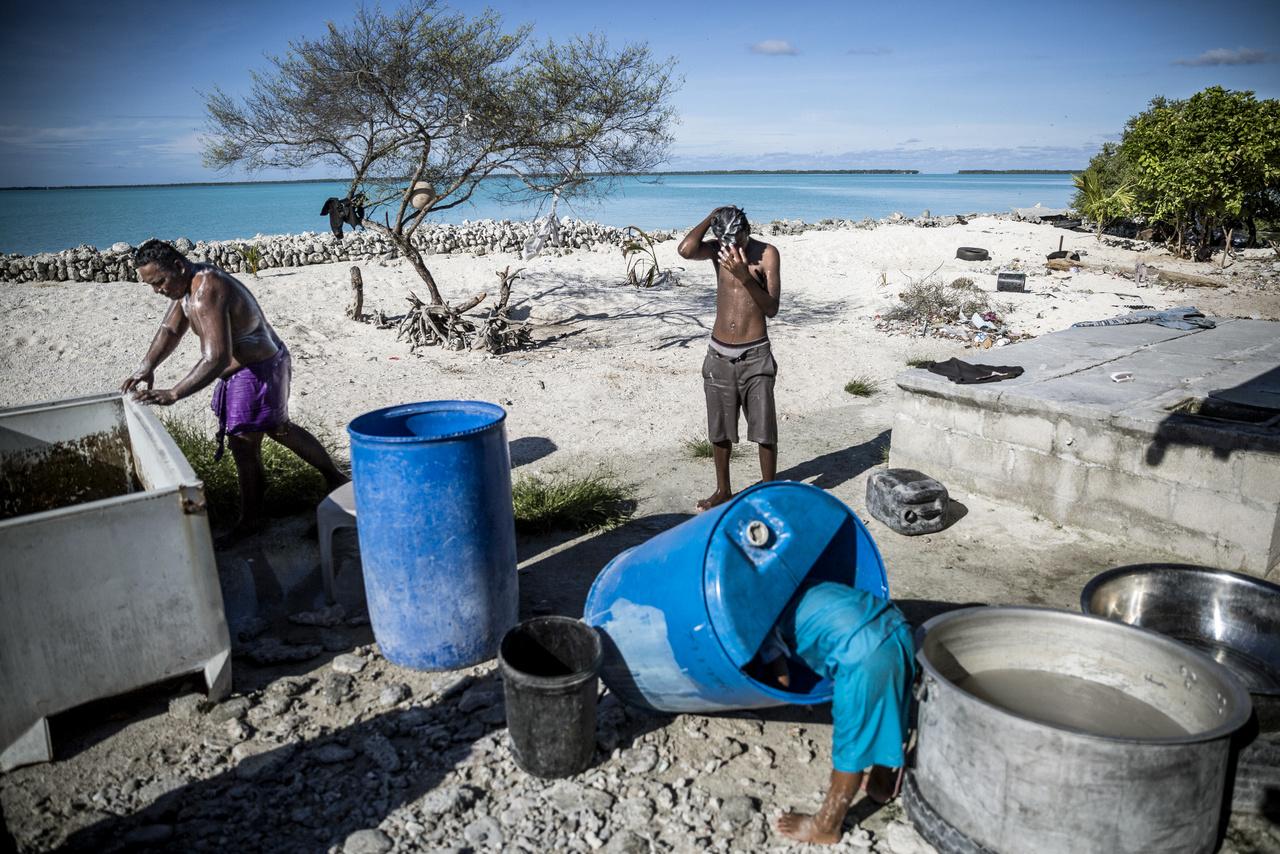 """Dagálykor  Tebikenikoora  falut rendszeresen elönti a víz, annak ellenére, hogy a helyiek falakkal próbálják távol tartani az óceánt. A nagyobb hullámoknak sajnos a saját kézzel vagy az önkormányzat által felhúzott akadályok sem állják útját, ezért a lakóházak és a kertek is állandó veszélyben vannak. """"A fal gyakran megsérül, de nincs pénzünk kijavítani. Amikor dagály van a házunkat víz veszi körül, de szerencsére nem jön be. Ha viszont szőkőár van akkor mindent eláraszt a tenger és a családomnak el kell menekülnie"""" - meséli Petero Tekiari. Itt éppen alacsony a vízállás, és a helyiek kihelyezett tartályokban mosnak ruhát.,"""