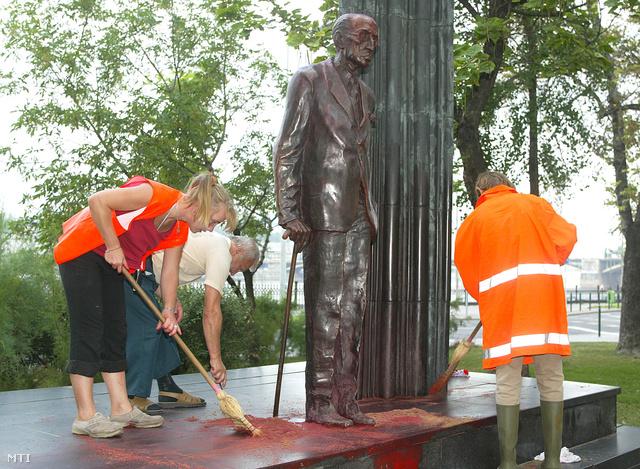 Budapest 2003. július 30.                         Vörös festékkel öntötték le Károlyi Mihály Kossuth téri szobrát Budapesten. A valamivel éjfél után érkezett állampolgári bejelentés után a rendőrök gyorsan a helyszínre értek és a Jászai Mari térnél elfogták a rongálás feltételezett tetteseit.                          A képen: a Fővárosi Közterület-fenntartó Rt. munkatársai tisztítják a szobrot.