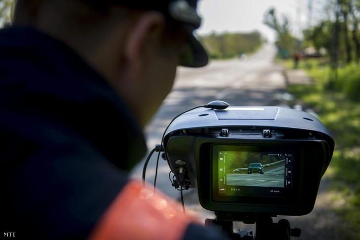 Egy rendőr a Véda automata közlekedés-ellenőrzési rendszer egyik sebességmérőjével a 6-os főúton Pécs határában 2016. április 21-én.