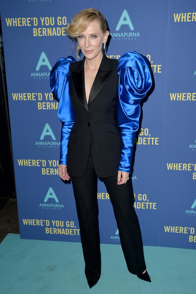Az outfit úgy néz ki, mint egy átlagos, hétköznapi nadrágkosztüm, kivéve a felsőrész királykék selyemből készült ujjait, és a hatalmas válltömést, amitől elég aránytalanná vált a színésznő alkata,..