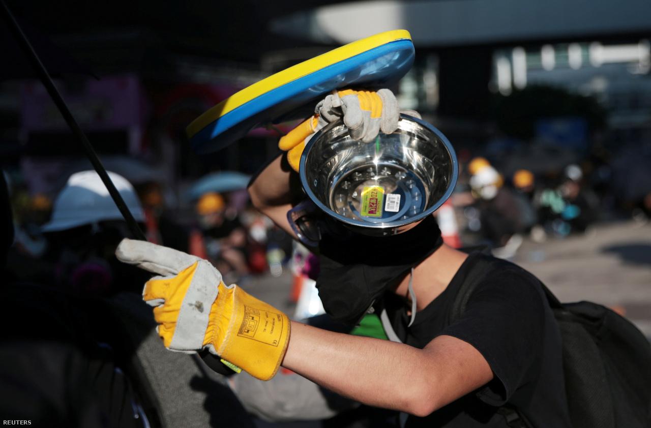 Az esernyőnél komolyabb védőeszközökkel is készülnek. Itt éppen a fejét próbálta biztosítani egy tüntető minden oldalról. A fekete maszkokra és pólókra is nagy volt a kereslet az elmúlt két hónapban, a legtöbb tüntető ilyenben van. Az egyszerű fekete ruhával könnyebben tudják titkolni személyazonosságukat, de olyanok is vannak, akik hazafelé tartva valahol átöltöznek, hogy még képek alapján se lehessen őket beazonosítani.