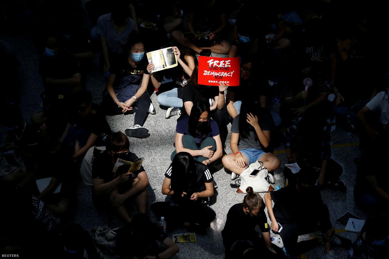 A reptér érkező oldalán megjelent tiltakozók. Múlt pénteken kezdtek ülősztrájkba tüntetők a reptéren. A helyzet egyre feszültebb lett, hétfőn végül blokádokkal megbénították a reptér forgalmát egy időre. Kedd hajnalban is 160 kimenő és 150 beérkező járatot törölt a Hongkongi Nemzetközi Repülőtér. Aznap este a hétfőinél is kaotikusabb jelenetek alakultak ki, rohamrendőrök hatoltak be a reptérre, ahol összecsaptak a tiltakozókkal. Végül aztán visszavonultak.