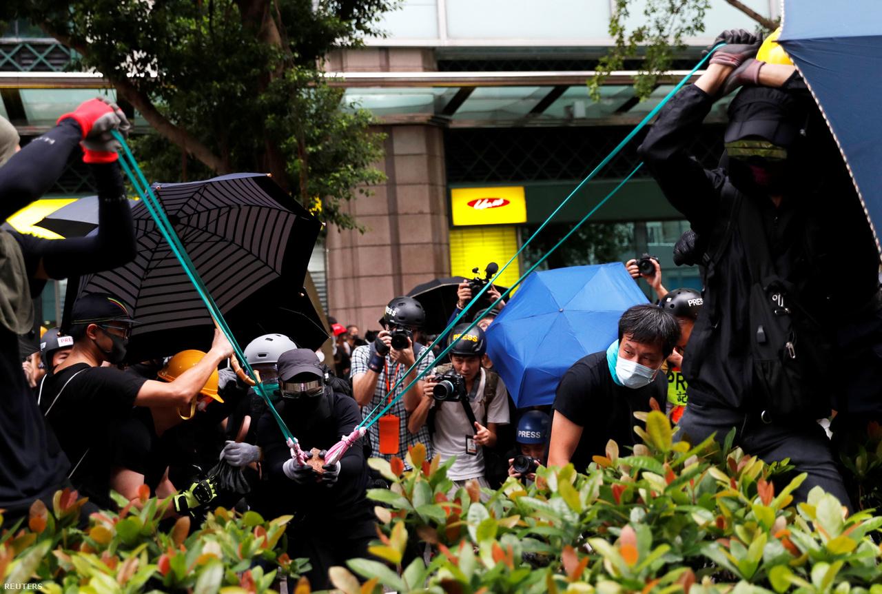 Óriási csúzlikat is rendszeresen bevetnek a tüntetők. A képen ketten kifeszítették, míg egy harmadik társuk törmelékdarabokat lőtt egy rendőrőrs felé. Mögöttük egy fekete zsákból veszik elő a következő lövedéknek való tárgyakat. A tüntetők azután kezdtek el téglákkal, Molotov-koktélokkal dobálni rendőrőrsöket, hogy a július 21-i demonstrációk után egy kormányközelinek tartott, fehérpólós és maszkos csoport tüntetőket vert. A triádokkal kötötték össze őket, és a tüntetők azzal vádolták a rendőröket, hogy nem avatkoztak közbe.