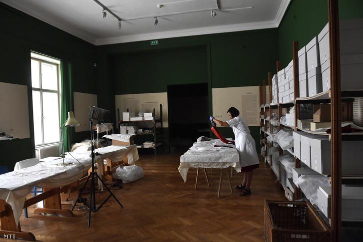 Tumpek Eta textilrestaurátor műtárgyakat rendez csomagoláshoz a Néprajzi Múzeumban 2019. augusztus 13-án.