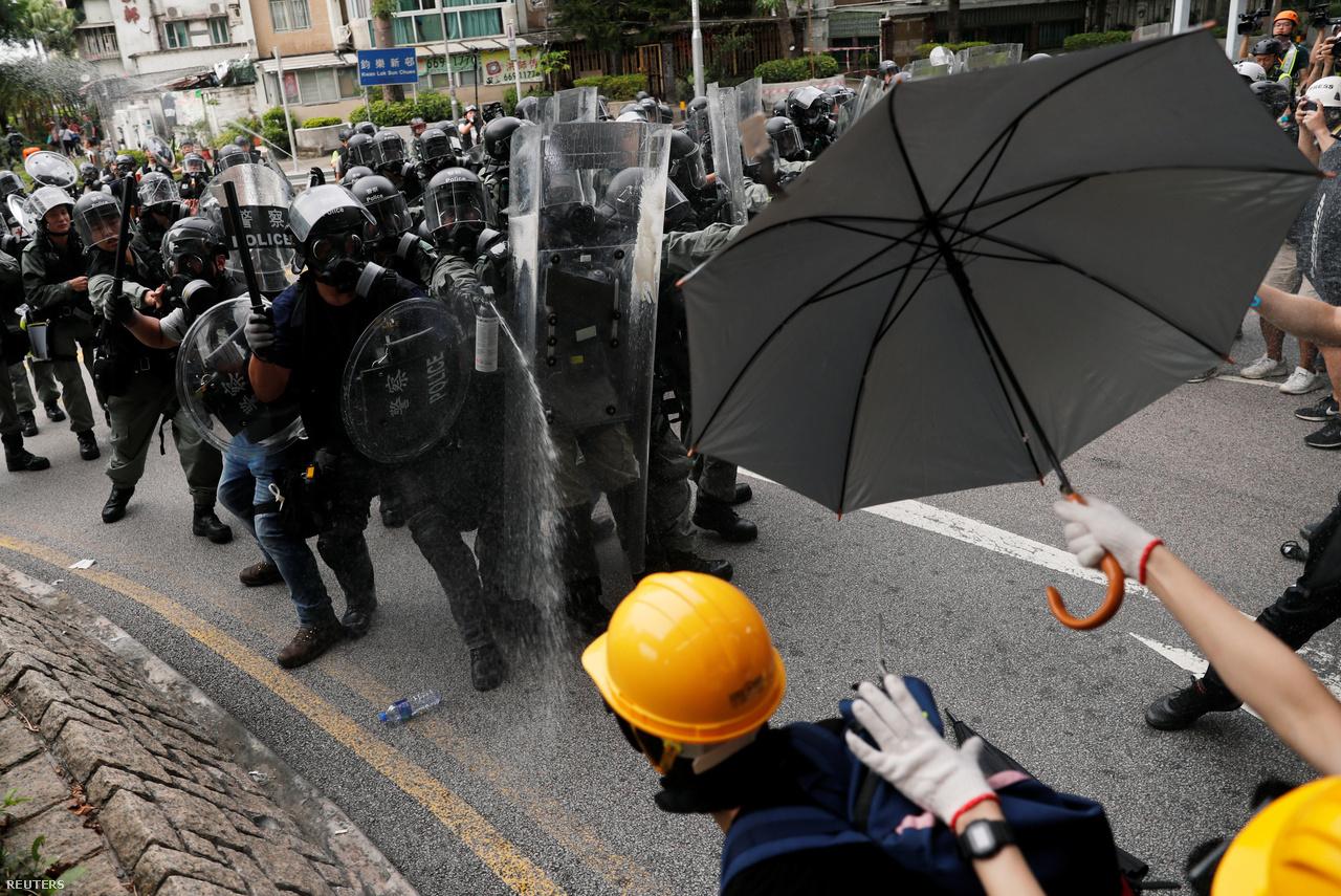 """Esernyők a paprikasprayt használó, pajzzsal és gumibottal felsorakozó rohamrendőrökkel szemben. A gázmaszkok és a szemüvegek a könnygáz mellett a paprikaspray ellen is szólnak, de a 2014-es megmozdulások szimbólumává váló esernyőknek is van ilyen funkciójuk. Takarásra is használják azonban az esernyőket, amíg például felszednek köveket, vagy leszerelnek korlátokat. Ha valaki felkiált: """"Most esik az eső!"""", akkor a közelben állók gyorsan odaszaladnak, és felnyitják az ernyőiket. Máskor pedig térfigyelőket is ernyőkkel fedtek be."""
