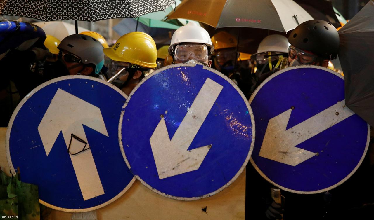 """Van, hogy már szinte egy római falanxra emlékeztetnek a felsorakozott tüntetők. Előre állnak azok, akik pajzsokat is hoztak magukkal, ebben az esetben leszerelt egyirányú utcát jelző táblákkal, de hátul is nyitott esernyőkkel próbálják kivédeni a könnygázgránátokat, és takarni a többieket. """"Vannak, akik az ételen spórolnak, és ahelyett is inkább védőfelszereléseket vesznek, főként a diákok"""" – mondta az egyik boltos a Reutersnek."""