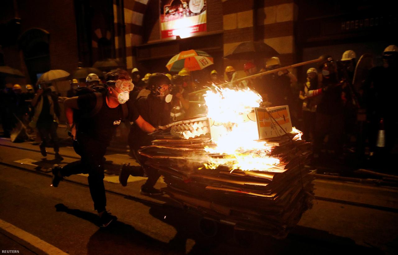 Meggyújtott dobozokat tolnak előre egy platformkocsin. A tüzek most a hagyományos Hungry Ghost Festival alatt is többeknél összekötődtek a tüntetésekkel. Ilyenkor füstölők és tüzek gyújtásával a szellemeknek és az ősöknek ajánlanak fel különböző tárgyakat, joss papírokat, amiket jelképesen elégetnek. A South China Morning Post szerint ezúttal több papíron is Carrie Lam hongkongi kormányzó arcképe volt. A pekingi vezetés bizalmát élvező Lam július 9-én halottnak nyilvánította a kiadatási tervezetet, de teljesen nem vonta vissza.