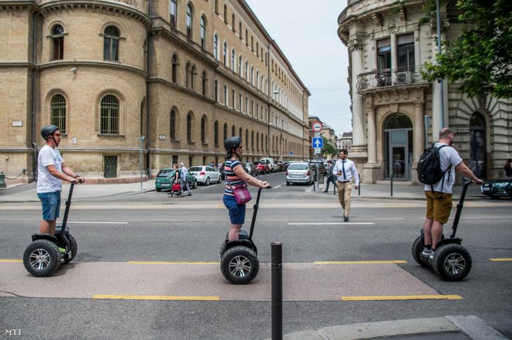 Turisták segwayen Budapesten az Alkotmány utcában