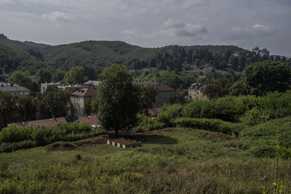 A közösségi kert négy emelt ágyása mögött sorakoznak a felújított bérházak a festői környezetben.