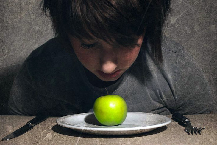 person looking at a green appleedited
