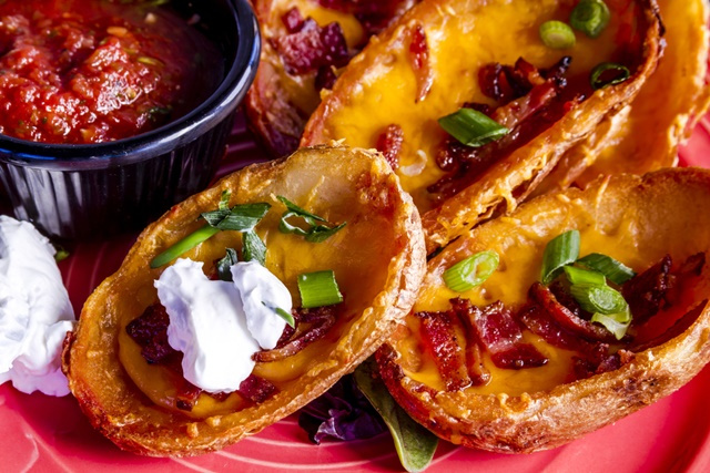 loaded potato skins appetizer filled with melted cheddar cheese,